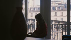 使用坐在公寓窗口的膝上型计算机的美丽的白种人CEO女实业家在有使的老房子视图惊奇巴黎 股票视频