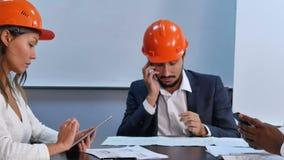使用坐在办公室的智能手机和数字式片剂的行政队 影视素材