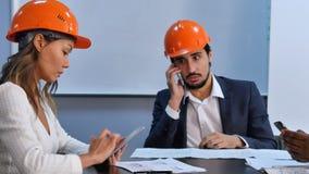 使用坐在办公室的智能手机和数字式片剂的行政队 免版税库存照片