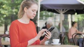 使用坐在咖啡馆大阳台的智能手机的年轻女人 股票视频