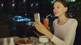 使用坐在餐馆的智能手机和drinck鸡尾酒汁液的愉快的妇女射击selfie在晚上 股票录像