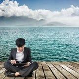 使用垫的亚裔商人和坐地面 免版税库存照片