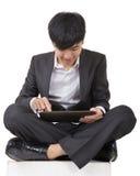 使用垫的亚裔商人和坐地面 免版税库存图片