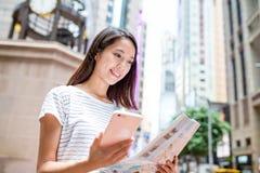 使用城市地图和手机的妇女 图库摄影