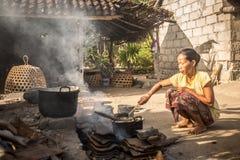 使用基本的精华,贫穷妇女烹调膳食 库存照片