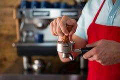 使用堵塞器的Barista按碾碎的咖啡入在咖啡馆的portafilter 免版税库存图片