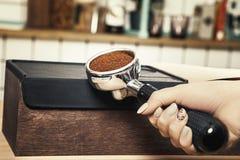 使用堵塞器, Barista按碾碎的咖啡 免版税库存照片