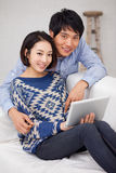 使用填充个人计算机的新亚洲夫妇 库存图片