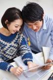 使用填充个人计算机的新亚洲夫妇 免版税库存照片
