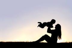 使用外面与笑的婴孩的愉快的母亲剪影 免版税库存照片