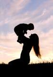 使用外面与婴孩的愉快的母亲剪影 免版税库存图片
