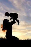 使用外面与婴孩的愉快的母亲剪影 免版税图库摄影