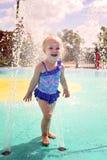 使用外面在水中的逗人喜爱的小小孩女孩在飞溅公园 免版税图库摄影