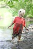 使用外面在河的泥泞的小男孩 库存图片