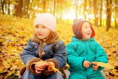 使用外面在秋叶的兄弟和姐妹 免版税图库摄影