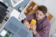使用多用电表的年轻技术员 库存照片