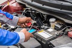 使用多用电表的技工手检查的电池 免版税库存照片