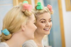 使用头发路辗的白肤金发的妇女 图库摄影