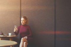 使用她巧妙的电话的少妇,当在当代咖啡店时坐 免版税库存照片