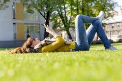 使用她巧妙的电话的少妇,当放置在草在她的午休的时公园 免版税库存图片