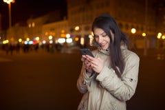 使用她巧妙的电话的欣快妇女和微笑对好消息消息 愉快的在一个巧妙的电话的妇女键入的正文消息 免版税库存照片