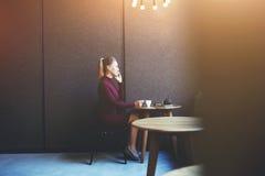 使用她巧妙的电话的确信的女实业家,当放松在工作天以后在咖啡店时 库存图片