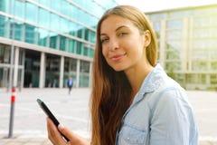 使用她智能手机坐的确信的女商人室外 免版税库存照片
