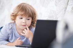 使用她的便携式计算机、孩子和technolo的聪明的小孩女孩 库存图片