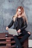 使用她的便携式计算机的年轻可爱的自由职业者女孩画象传送信息和搜寻关于互联网的信息 图库摄影