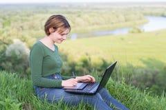 使用她的图形输入板的美丽的女孩坐在草在河附近 库存图片