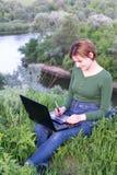 使用她的图形输入板的美丽的女孩坐在草 免版税图库摄影