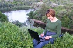使用她的图形输入板的美丽的女孩坐在草 库存照片