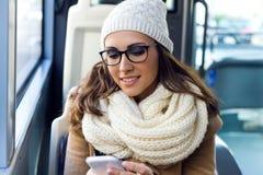 使用她的在公共汽车的年轻美丽的妇女手机 免版税库存照片