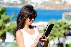 使用她的在海背景的美丽的妇女片剂 免版税库存照片