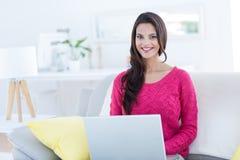 使用她的在长沙发的微笑的美丽的浅黑肤色的男人膝上型计算机 库存图片