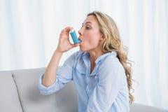 使用她的在长沙发的金发碧眼的女人哮喘吸入器 库存照片