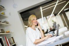 使用她的手机和sitti的白肤金发的白种人女实业家 免版税图库摄影