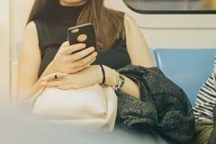 使用她的手机的妇女在地铁 库存照片