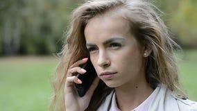 使用她的手机的美丽的女孩,室外 轻松的小姐画象在夏天公园谈话在电话 股票视频