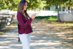 使用她的手机的美丽的女孩画象在城市 免版税库存图片