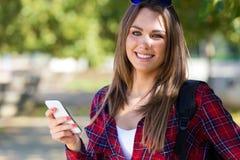 使用她的手机的美丽的女孩画象在城市 免版税图库摄影