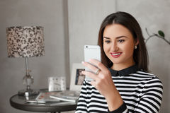 使用她的手机的美丽的小姐画象为与朋友的通信 库存图片