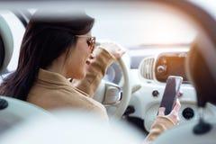 使用她的手机的美丽的少妇在汽车 免版税库存图片