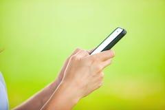 使用她的手机的美丽的少妇 免版税库存照片