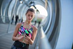 使用她的手机的运动少妇和听到音乐为行使 库存照片