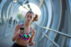 使用她的手机的运动少妇和听到音乐为行使 免版税库存图片