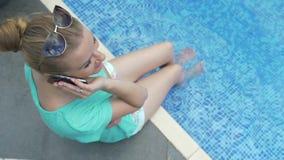 使用她的手机的年轻可爱的妇女在假日在水池附近 影视素材