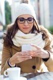 使用她的手机的年轻美丽的妇女在咖啡馆 库存图片
