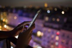 使用她的手机,城市地平线夜光backgro的妇女 免版税库存图片