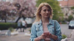 使用她的手机,繁忙的小姐沿着走街道 有风的天气 牛仔裤穿戴 汽车,赶紧人和 影视素材
